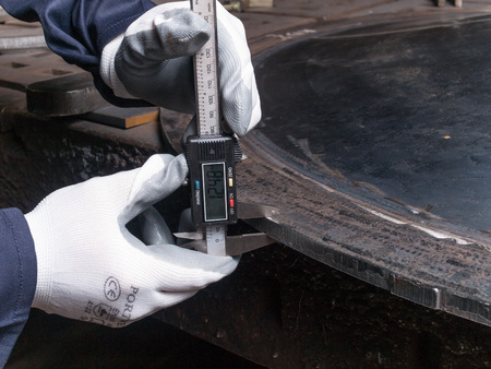 thickness: Digital measuring device measuring the thickness of a metal plate
