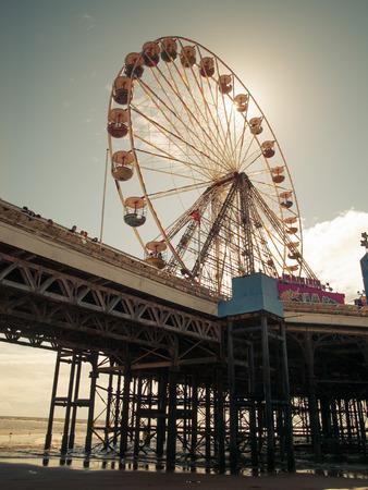 big wheel: England, Blackpool, 04222015, Blackpool south piers big wheel with sun flare vintage feel. Editorial