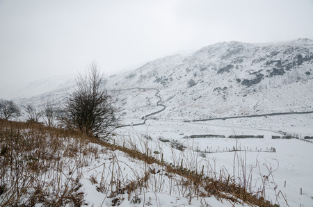 lake district england: Snowy mountains in the lake district in england, with a stone wall disappearing into the distance.