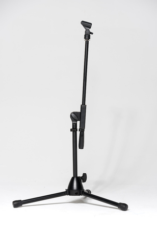 microphone stand: empty microphone stand against a white studio background