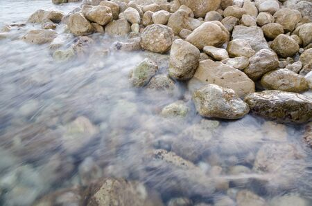 sooth: A slow shutter speed captures clear sea water washing over rocks
