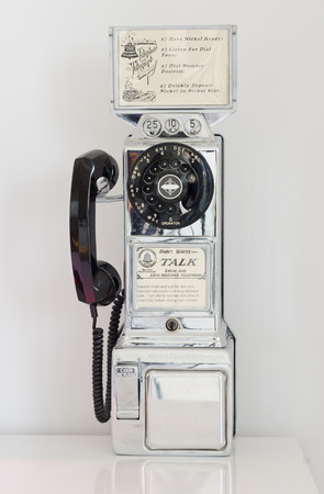 phon: Barcelona, Spain, 05062014, Retro nickel coin, long distance chrome telephone in a clean white vintage boutique
