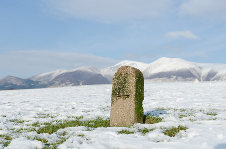 blustery: The Lake District, Keswick, England, 01172016, Snowy field stone marker with snow covered mountains in the background Editorial