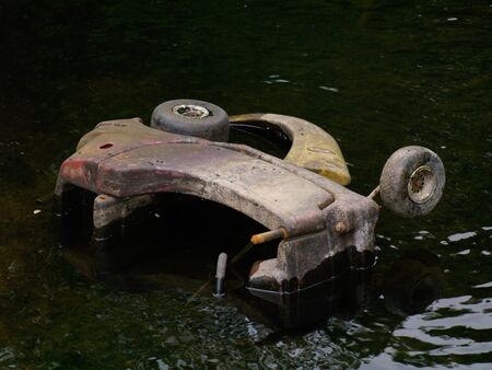 drained: abandoned childrens toy buggy in a drained canal