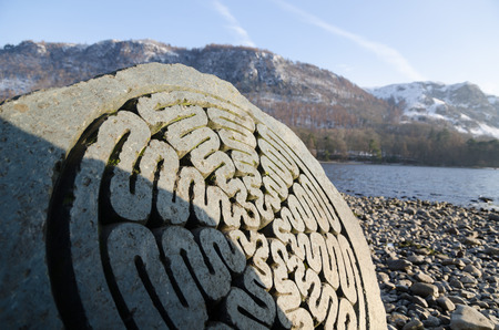 borrowdale: The Lake District, Keswick, England, 01172016, Winter lakeside view with carved stone memorial in the foreground