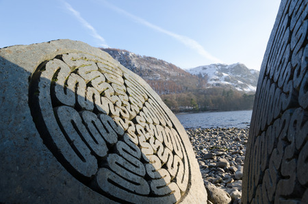 blustery: The Lake District, Keswick, England, 01172016, Winter lakeside view with carved stone memorial in the foreground