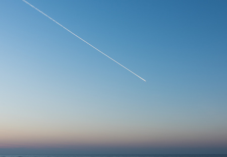 White Condensation Trail From an aeroplane flying across a beautiful blue and pink sunset sky Stock Photo