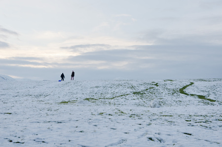 blustery: The Lake District, Keswick, England, 01172016, People sledging in the Winter snow