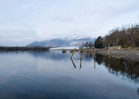 borrowdale: The Lake District, Keswick, England, 01172016, Winter lakeside view with jetty mooring posts and snowy mountains in the background Editorial