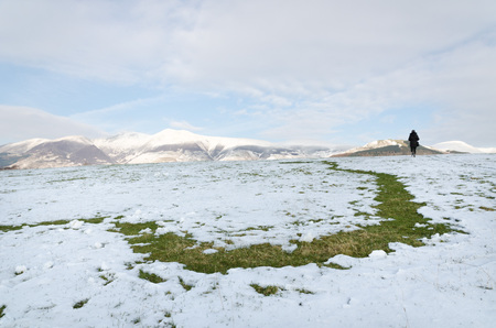 The Lake District, Keswick, England, 01172016, Snowy field with snow covered mountains in the background