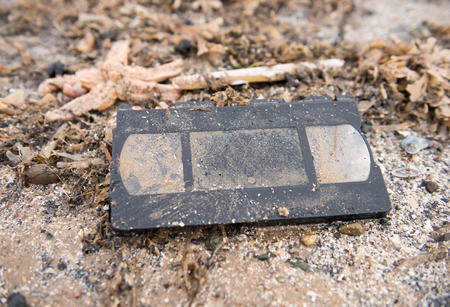 Old retro vas tape washed up on a beach, surrounded by seaweed with a shallow depth of field.