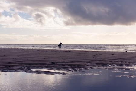 femme a cheval: Silhouette d'un cheval de femme � cheval libre sur une plage couvert de pourpre au coucher du soleil Banque d'images
