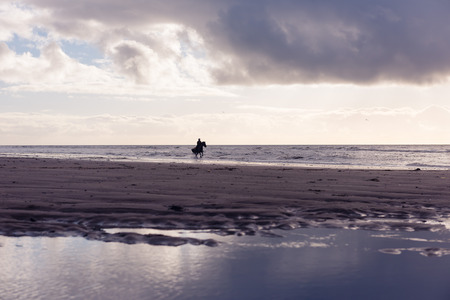 free riding: Silhouette of a woman horse riding free on a purple overcast beach at sunset