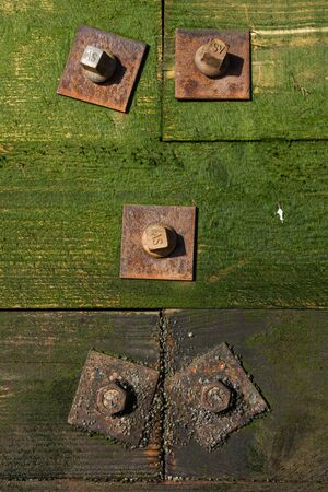 camoflauge: Rusty metal nuts and bolts, holding together a green algae covered wooden sea wall Stock Photo