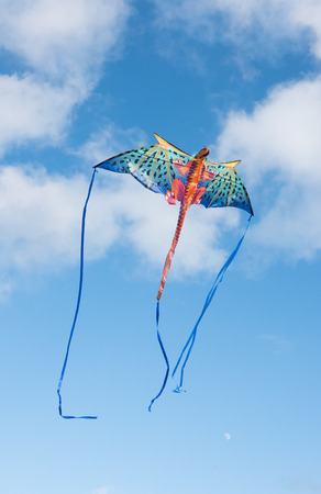 take a breather: Mythical dragon kite flying in a cloudy sky on a bright sunny day