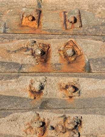 camoflauge: Rusty metal nuts and bolts, holding together a weathered wooden sea wall Stock Photo