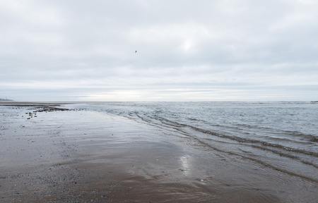 calming: relaxing and gentle calming waves flowing into a beach on an gloomy overcast day Stock Photo