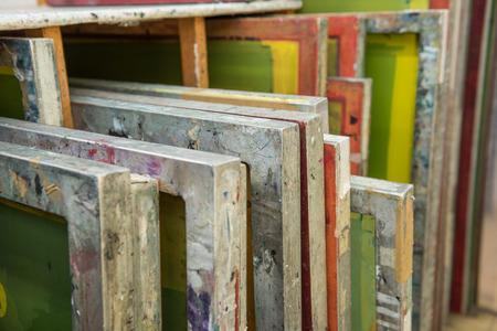 imprenta: pantallas de serigrafía de seda almacenados en un estante de madera listos para su impresión. Foto de archivo