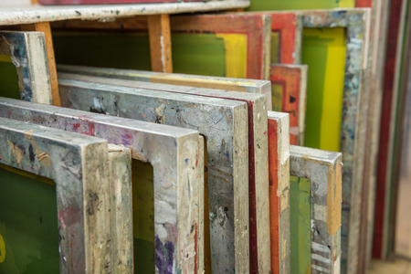 hand print: Silk screen printing screens stored in a wooden rack ready for printing.