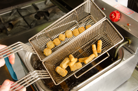 industrial kitchen: A silver deep pan industrial kitchen oil fryer, with golden oil, bubbling and frying potatoes