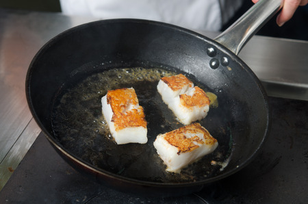 non: Pan fried golden fish fillet cubes, frying in real butter, in a non stick rustic pan.