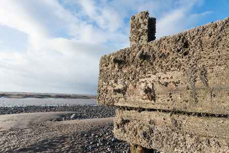 cleveleys, england, 02172016, A rustic, weathered wooden sea defence wall, showing signs of damage and barnacle growth