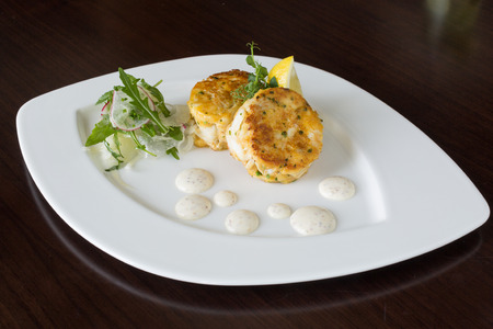 Beautiful fresh golden fish cakes, served with a wedge of lime, dill sauce and rocket on a white plate