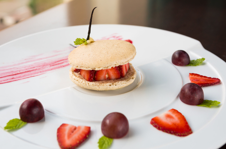 serves: fresh strawberry and cream macaroons serves with grape and strawberry segments Stock Photo