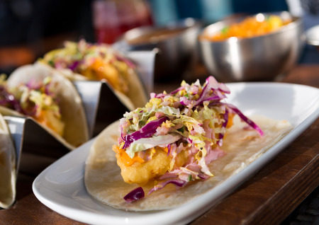 international food: Mexican fried cod fish taco served with lettuce, red onion and sauce Stock Photo