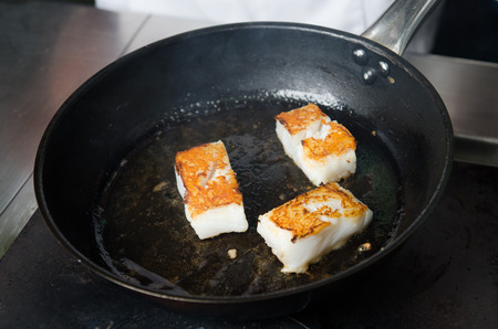 leavings: Pan fried golden fish fillet cubes, frying in real butter, in a non stick rustic pan.