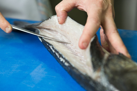 filleting: Filleting and removing the bone from a fresh fish on a blue cutting board using a sharp knife.