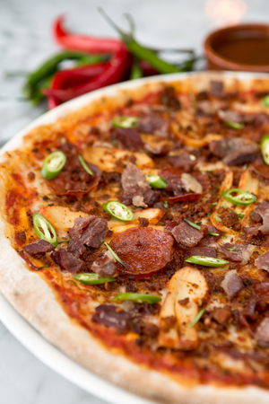 meat lover: Spicy pepperoni, chicken and bacon pizza with jalape?o slices and chilli peppers in the background