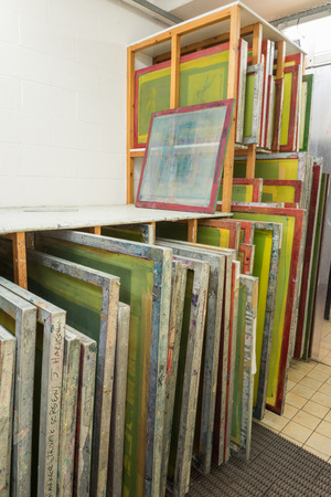 silk screen: Silk screen printing screens stored in a wooden rack ready for printing.