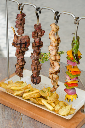 Cooked Chicken, beef and vegetable kebab skewers hanging from a rack, served with fries, and ready to eat. Stock Photo