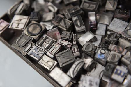 Vintage lead letterpress printing blocks against a weathered metal drawer background with bokeh.