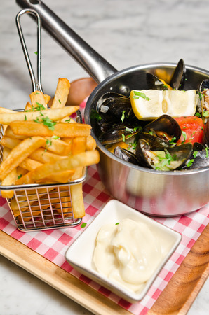 lemon wedge: Pan cooked garlic mussels in a white wine sauce served with french fries, lemon wedge and white sauce.