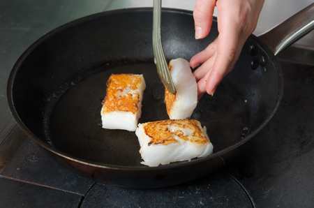 Pan fried golden fish fillet cubes, frying in real butter, in a non stick rustic pan.