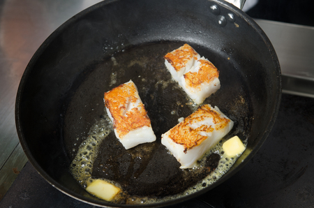 non stick: Pan fried golden fish fillet cubes, frying in real butter, in a non stick rustic pan.