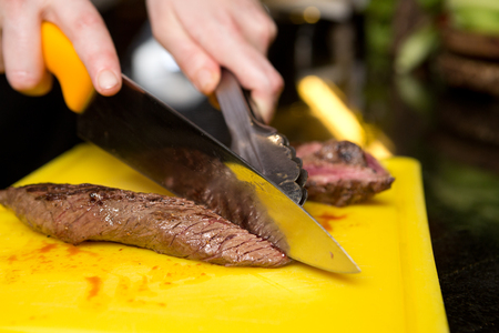 skippy: Cutting flame grilled, cooked kangaroo steak loin on a yellow cutting board