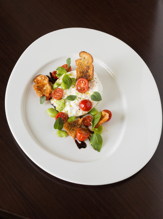 balsamic vinegar: Delicious tomato and mozzarella cheese salad caprese, served on a white plate, with basil, croutons and balsamic vinegar.