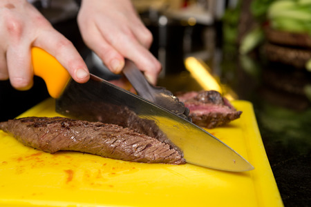 Cutting flame grilled, cooked kangaroo steak loin on a yellow cutting board