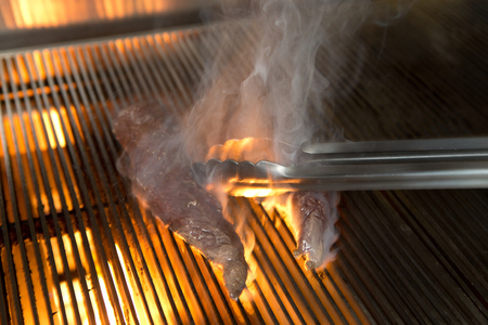 skippy: Cooking kangaroo steak on a flame grill griddle on high flame