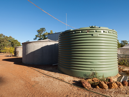 Large green rainwater collection tank and concrete tank, on a farm in Australia Stock fotó
