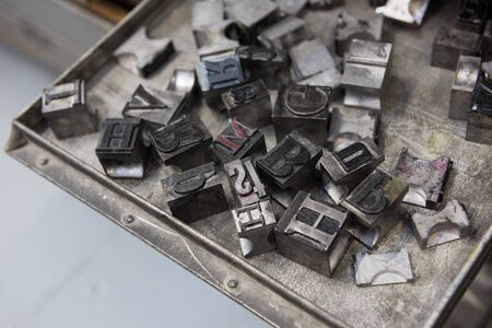 typesetter: Vintage lead letterpress printing blocks against a weathered metal drawer background with bokeh.