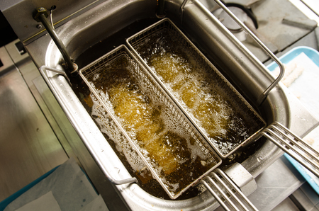 bubbling: A silver deep pan industrial kitchen oil fryer, with golden oil, bubbling and frying potatoes
