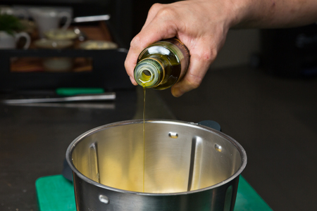 extra virgin olive oil: Extra virgin olive oil being poured into a metal mixing bowl. Stock Photo