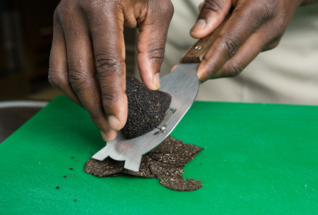 blackness: Expensive gourmet Black truffle being sliced thinly on a green cutting board