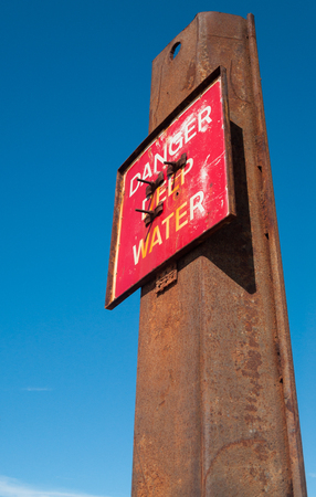 don't care: Red danger deep water warning hazard sign on a rusty metal beam. Stock Photo