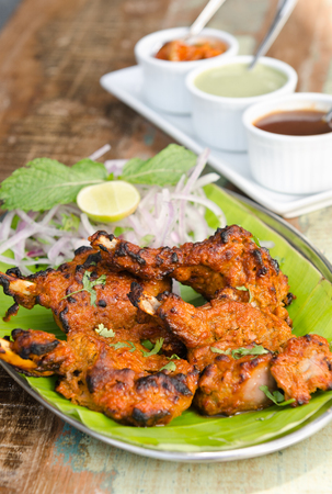 tandoori chicken: Delicious tandoori chicken starter, served with lime, onion, mint, yoghurt and sauces, on a banana leaf base.