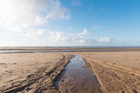 indent: Beautiful blue sky and textured sand, on a cool sunny winters day at the beach